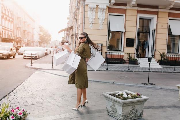 Портрет в полный рост вдохновленной женщины в блестящих туфлях, наслаждающейся покупками