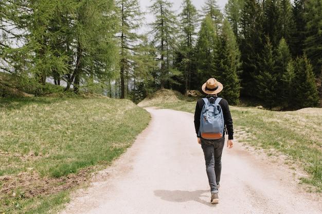 휴가에 여름 숲을 탐험하는 남성 여행자의 뒤에서 전신 초상화