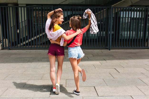 Ritratto a figura intera dal retro di ragazze formose con gambe lunghe che si divertono all'aperto e si abbracciano