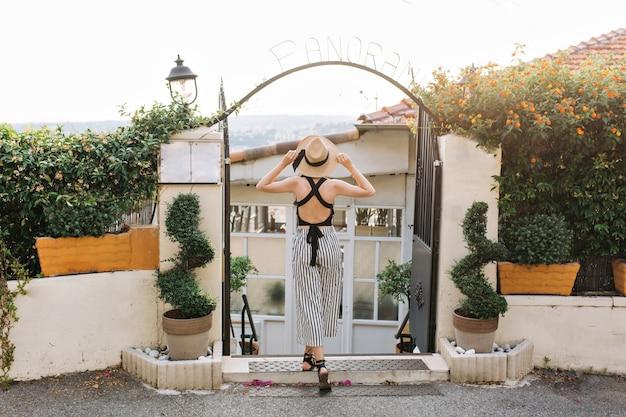 Ritratto a figura intera dalla parte posteriore della donna in cappello e abbigliamento a strisce in piedi con le gambe incrociate davanti a cancelli di ferro nero