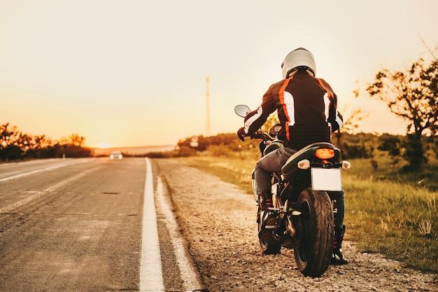 日没に対して新しい場所を見つけるために彼の自転車で旅行を始める準備ができている彼のオートバイのヨーロッパのバイカーの後ろからの完全な長さの肖像画。