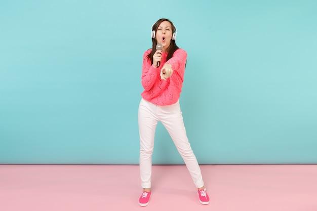 Портрет веселой женщины в полный рост в вязаном свитере, белых штанах, наушниках поет песню в микрофон