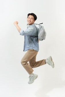 Full length portrait of a funny cheerful male student jumping on white background