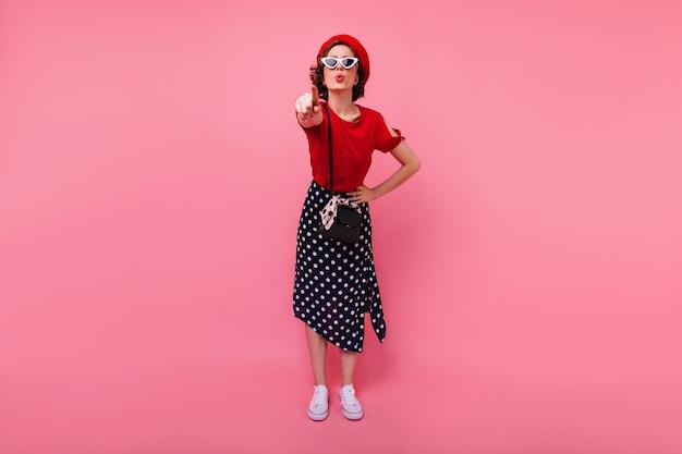 Ritratto integrale del dito puntato divertente della ragazza francese. magnifica donna caucasica in gonna lunga in piedi sul muro rosa.