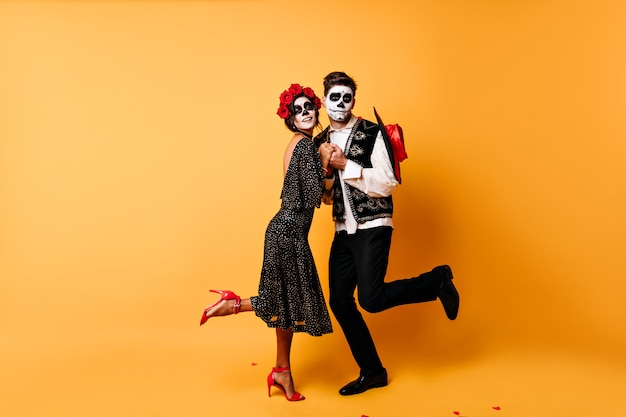 Full-length portrait of funny zombies dancing . indoor photo of dead couple celebrating halloween together.