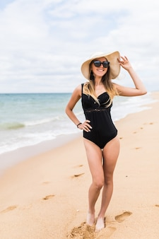 Full-length portrait of gorgeous young woman in straw hat walking on sandy beach