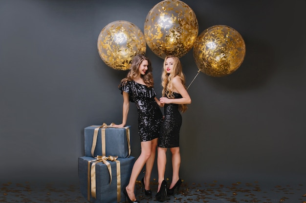 Full-length portrait of graceful girl with trendy hairstyle touching gift box and laughing. two ecstatic ladies posing with golden balloons.