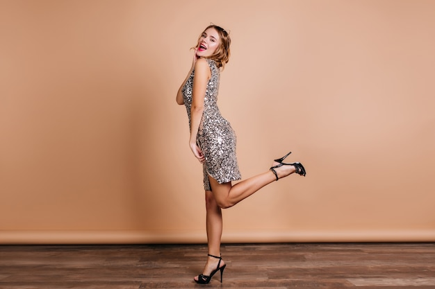 Full-length portrait of graceful lady in trendy shining dress having fun in new high heel shoes