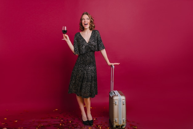 Full-length portrait of graceful white female model drinking wine before trip