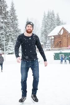 Full length portrait of a handsome man ice skating outdoors with snow