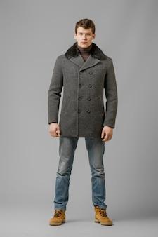 Full length portrait of handsome man in warm coat posing in studio