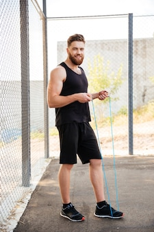 Full length portrait of a happy bearded fitness man workout with jumping rope outdoors