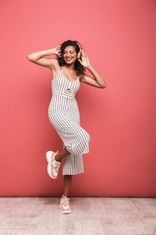Full length portrait of a happy beautiful young woman wearing summer clothing jumping isolated over pink wall, listening to music with wireless earphones, dancing