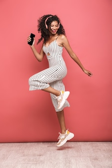 Full length portrait of a happy beautiful young woman wearing summer clothing jumping isolated over pink wall, listening to music with wireless earphones, holding blank screen mobile pho