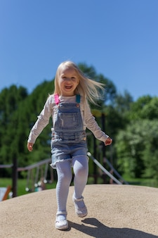 Full length portrait of happy blonde 4 years girl playing on playground outdoors against green trees and blue sky
