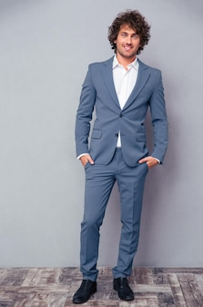 Full length portrait of a happy businessman standing on gray wall and looking at front