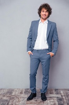 Full length portrait of a happy businessman with curly hair standing on gray wall and looking at front