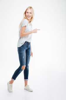 Full length portrait of a happy casual woman pointing finger away isolated on a white wall