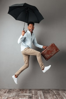 Full length portrait of a happy cheerful african man jumping