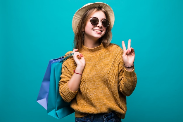Full length portrait of a happy excited woman in bright colorful clothes holding shopping bags while standing and showing peace gesture isolated on green wall