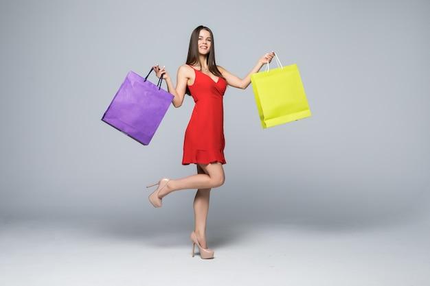 Ritratto integrale di una donna emozionante felice in vestito rosso che sta e che tiene i sacchetti della spesa variopinti isolati su una parete bianca
