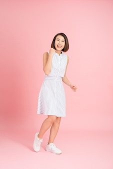 Full length portrait of happy exited pretty girl in elegant light blue dress looking at camera while jumping over pink background