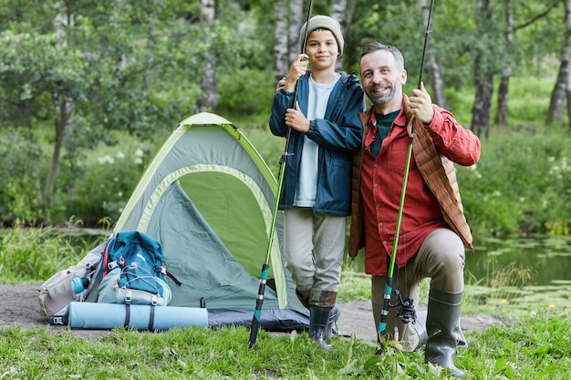 Full length portrait of happy father embracing son while enjoying fishing trip together and smiling at camera , copy space