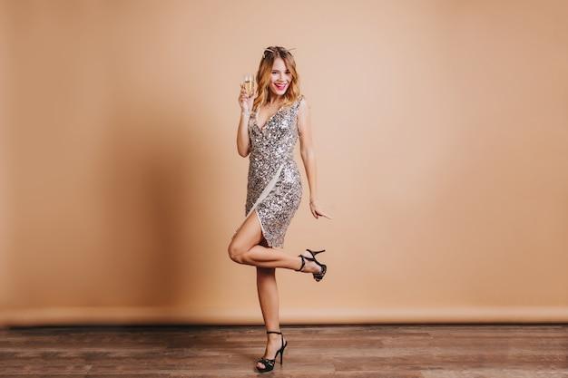Full-length portrait of happy female model in stylish dress standing on one leg on beige wall, celebrating christmas
