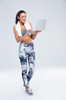 Full length portrait of a happy fitness woman using laptop isolated on a white wall