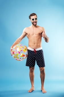 Full length portrait of a happy guy holding beach ball