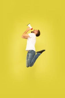 Full length portrait of happy jumping man isolated on yellow background. caucasian male model in casual clothes. freedom of choices, inspiration, human emotions concept. calling with mouthpeace.