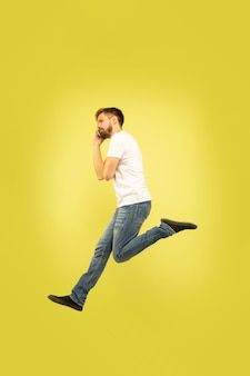Full length portrait of happy jumping man isolated on yellow background. caucasian male model in casual clothes. freedom of choices, inspiration, human emotions concept. hurry up, talking on phone.
