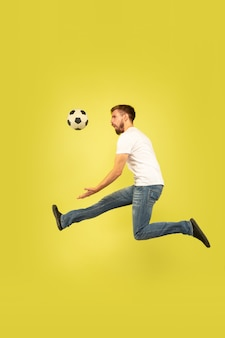 Full length portrait of happy jumping man isolated on yellow background. caucasian male model in casual clothes. freedom of choices, inspiration, human emotions concept. playing football on the run.