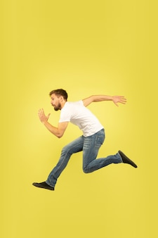 Full length portrait of happy jumping man isolated on yellow background. caucasian male model in casual clothes. freedom of choices, inspiration, human emotions concept. run for sales, hurry up.