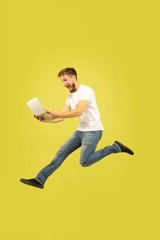 Ritratto integrale dell'uomo di salto felice isolato su colore giallo