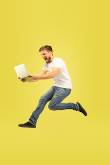 Full length portrait of happy jumping man isolated on yellow