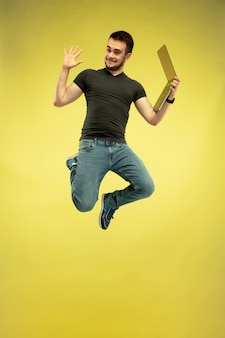 Full length portrait of happy jumping man with gadgets isolated on yellow background. modern technologies, freedom of choices concept, emotions concept. using laptop for work and fun in flight.