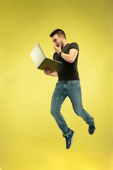 Full length portrait of happy jumping man with gadgets isolated on yellow background