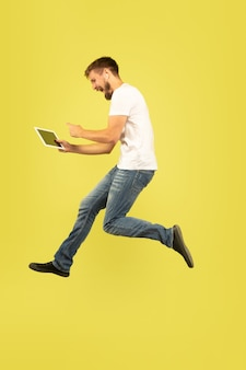 Full length portrait of happy jumping man on yellow background