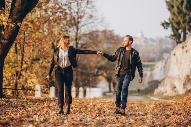 Full length portrait of a happy loving couple walking outdoor in the autumn park