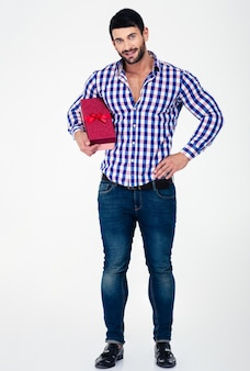 Full length portrait of a happy man holding gift box isolated on a white wall