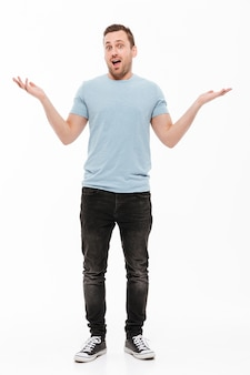 Full-length portrait of happy man with stubble in casual throwing up arms, expressing surprise or excitement