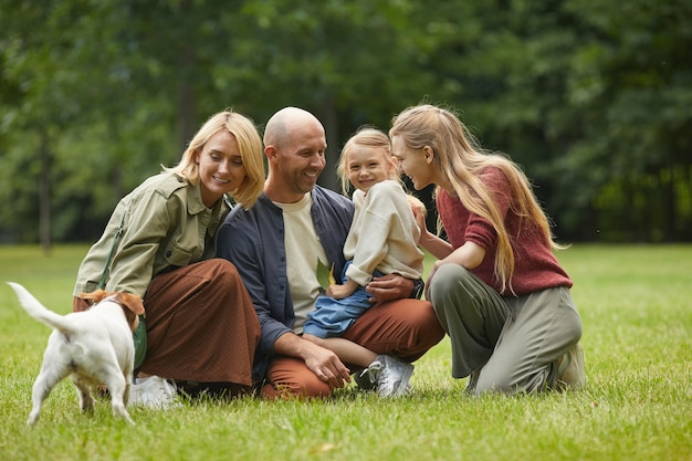 Full length portrait of happy modern happy family with two daughters and pet dog sitting on green grass outdoors and enjoying time in park together