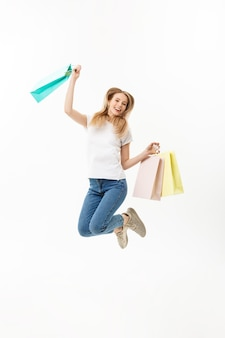 Ritratto integrale di una ragazza graziosa felice che tiene le borse della spesa mentre salta e guarda la telecamera isolata su sfondo bianco.