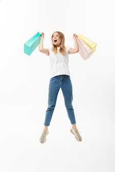 Full length portrait of a happy pretty girl holding shopping bags while jumping