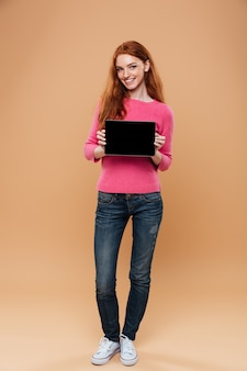 Full length portrait of a happy pretty redhead girl pointing finger at digital tablet