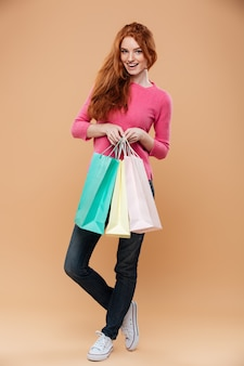 Full length portrait of a happy pretty redhead girl with shopping bags