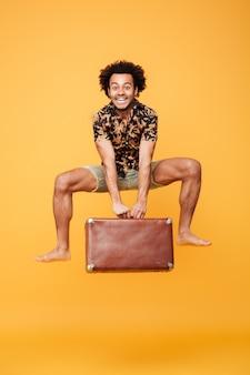 Ritratto integrale di un giovane uomo africano felice che salta