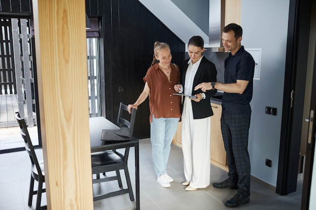 Full length portrait of happy young couple talking to real estate agent while buying new house, copy space