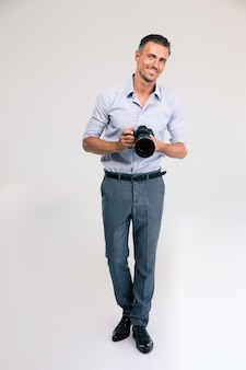 Full length portrait of a happy young man holding camera isolated